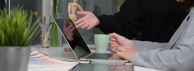 Vista lateral de dos diseñadores discutiendo sobre su proyecto en una sala de oficina con mampara