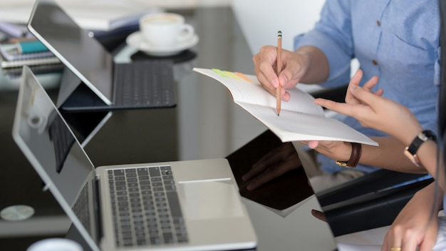 Vista lateral de dos empresarios haciendo una lluvia de ideas sobre su tarea en la mesa negra