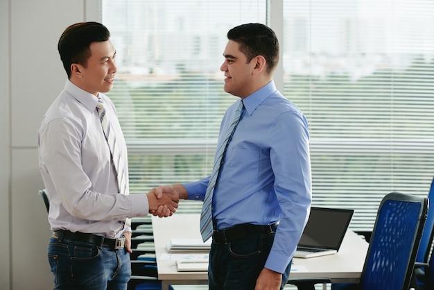 Vista lateral de dos gerentes dando un apretón de manos para saludarse en la oficina