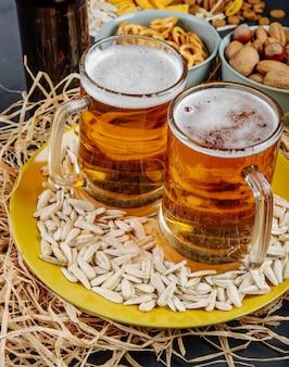 Vista lateral de dos jarras de cerveza en un plato con semillas de girasol en paja