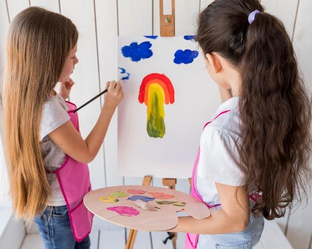 Vista lateral de dos niñas pintando en el lienzo con pincel.