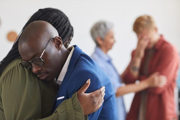 Vista lateral de dos personas afroamericanas que se abrazan durante la reunión del grupo de apoyo, ayudándose mutuamente con el estrés, la ansiedad y el dolor, copie el espacio