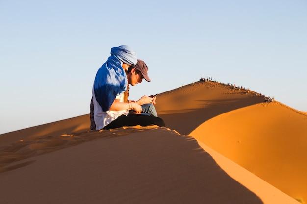 Vista lateral de dos personas sentadas en la duna