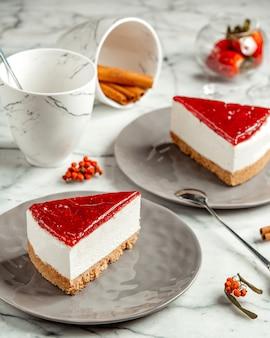 Vista lateral dos tarta de queso de fresa con una taza de té y canela