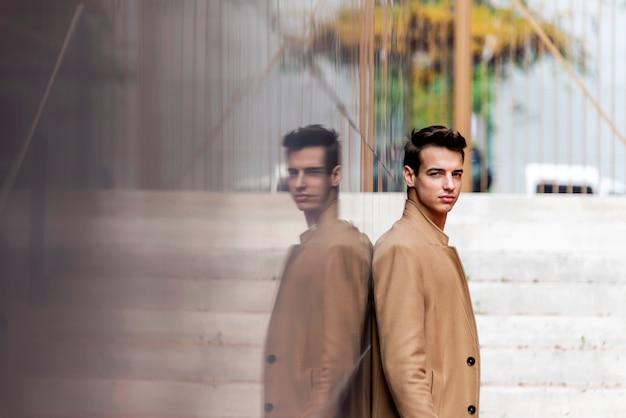 La vista lateral del dril de algodón que lleva del hombre elegante joven viste inclinarse en una pared mientras que mira la cámara al aire libre en día soleado