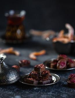 Vista lateral de dulces de chocolate servidos con té en una pared negra