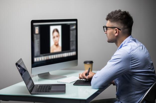 Vista lateral de un editor de fotos de hombre con tableta gráfica en una oficina luminosa