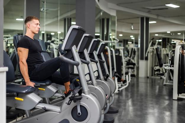 Vista lateral ejercicio masculino en bicicleta