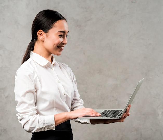 Vista lateral de una empresaria asiática joven que mira la computadora portátil que se sostiene a disposición contra fondo gris