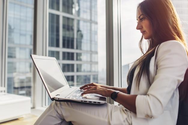 Vista lateral de la empresaria confía en usar portátil sentado en el moderno centro de negocios.