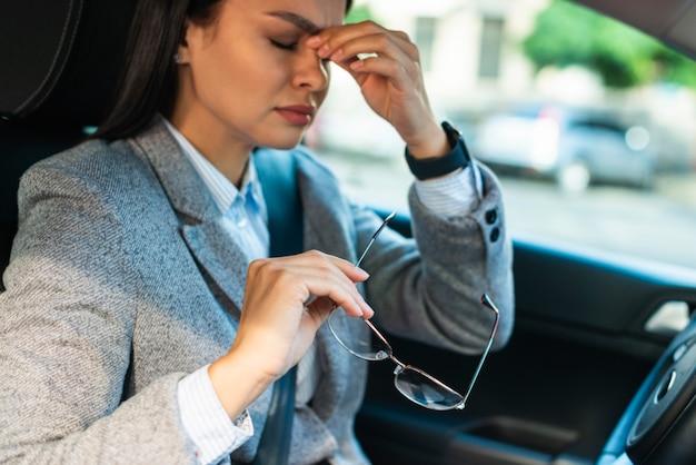 Vista lateral de la empresaria con dolor de cabeza en el coche
