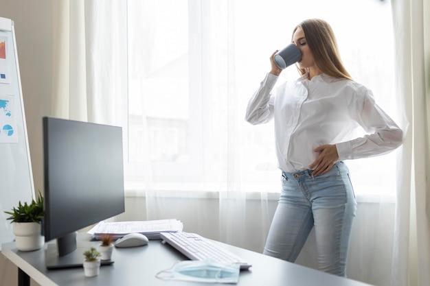 Vista lateral de la empresaria embarazada tomando un café en la oficina
