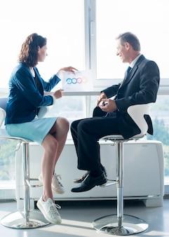 Vista lateral de una empresaria explicando hoja de elementos de infografía a su colega