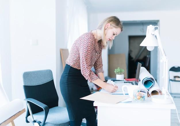 Vista lateral de una empresaria joven que se coloca cerca de la escritura del escritorio en oficina