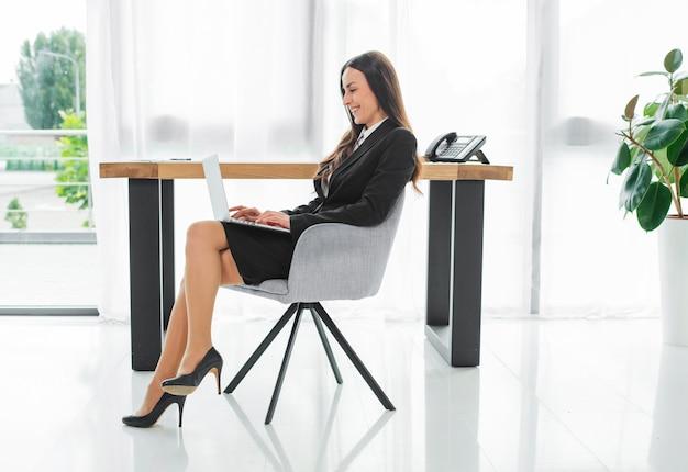 Vista lateral de una empresaria joven que se sienta delante del escritorio usando la tableta digital