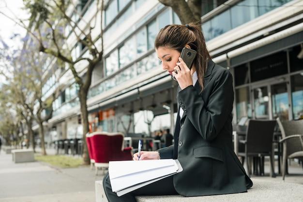 Vista lateral de una empresaria joven sentada fuera del edificio escribiendo en la carpeta con la pluma