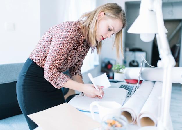 Vista lateral de una empresaria mirando nota adhesiva y pluma en su mano