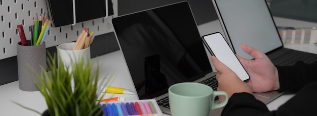 Vista lateral de la empresaria que trabaja con el teléfono inteligente maqueta en mesa blanca