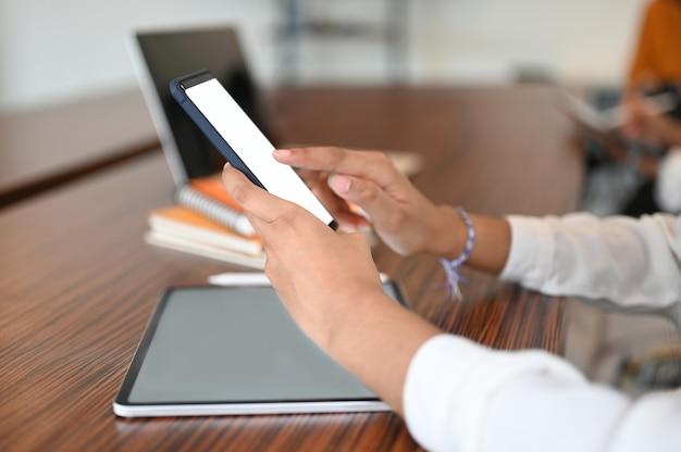 Vista lateral de la empresaria sosteniendo teléfono móvil de pantalla en blanco mientras trabaja con tableta digital en escritorio de madera.