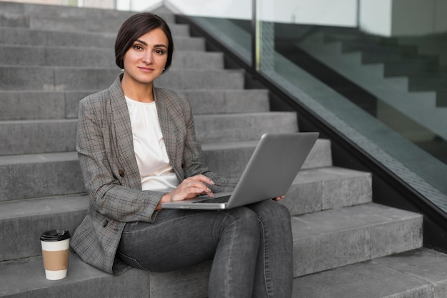 Vista lateral de la empresaria tomando café y trabajando en la computadora portátil en pasos