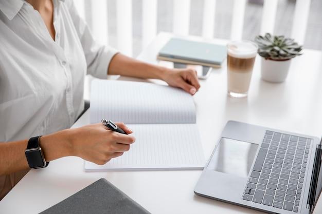 Vista lateral de la empresaria trabajando con portátil y portátil