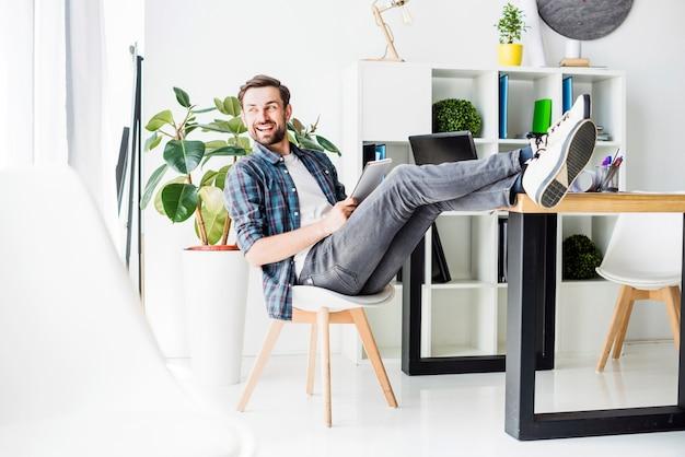 Vista lateral de un empresario feliz relajado sentado en la oficina