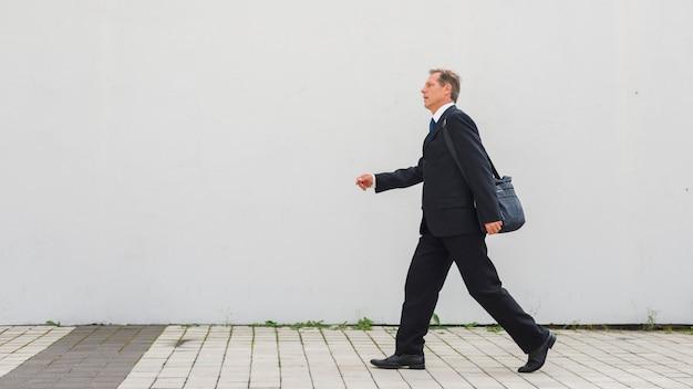Vista lateral de un empresario maduro caminando sobre el pavimento