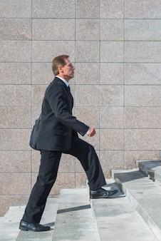 Vista lateral de un empresario maduro subiendo escaleras