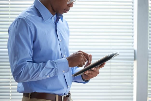 Vista lateral del empresario recortado revisando las noticias mundiales en la tableta de pie en la oficina
