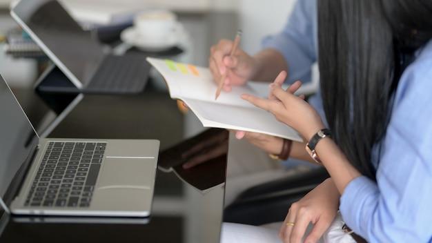Vista lateral de empresarios discutiendo sobre su trabajo mientras mira en el cuaderno