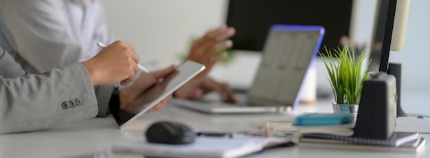 Vista lateral de empresarios que trabajan junto con tabletas, computadoras portátiles, suministros de oficina