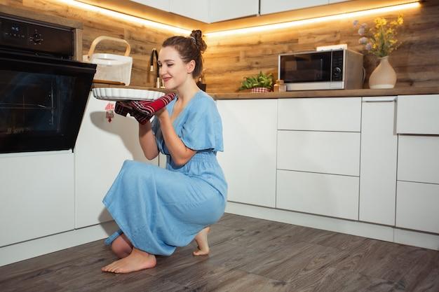 Vista lateral de la encantadora mujer rubia rizada caucásica en delantal que saca del horno alimentos horneados. interior de cocina doméstica. mujer tomando bandeja para hornear. concepto de cocina casera.