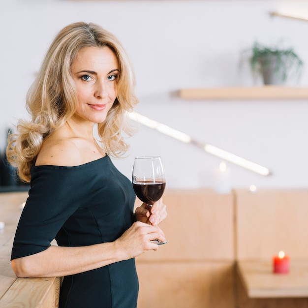 Vista lateral de la encantadora mujer sosteniendo una copa de vino