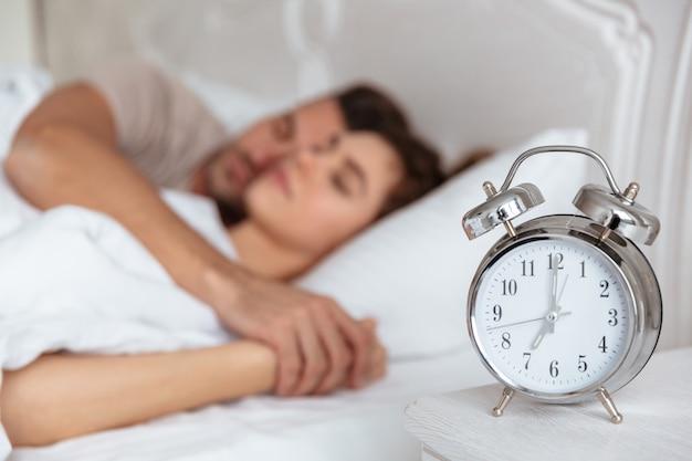 Vista lateral de la encantadora pareja durmiendo juntos en la cama