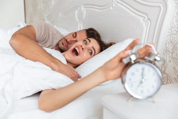 Vista lateral de la encantadora pareja sorprendida durmiendo juntos en la cama