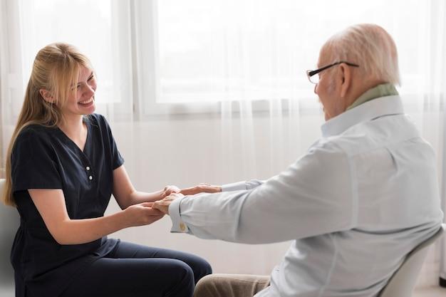 Vista lateral de la enfermera sosteniendo las manos del hombre mayor