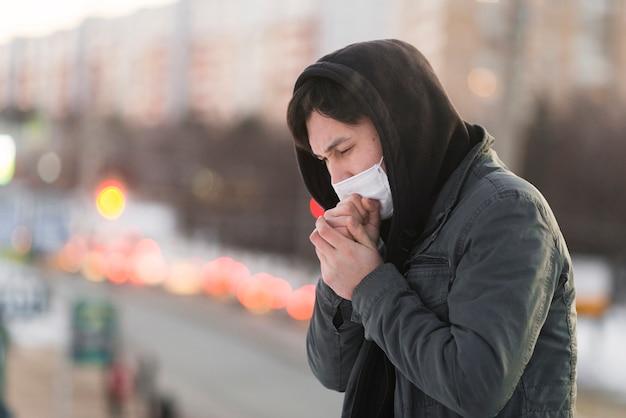Vista lateral del enfermo tosiendo con espacio de copia