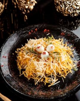 Vista lateral de ensalada de atún con sheese y huevos de codorniz en un plato sobre placa negra