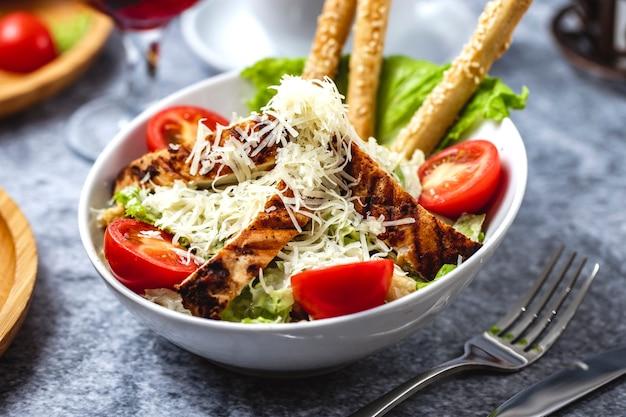 Vista lateral ensalada césar con pollo a la parrilla, parmesano, tomate, lechuga y palitos de pan