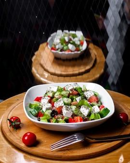Vista lateral de ensalada fresca con queso feta, tomates, pepinos y hierbas secas con aceite de oliva en un tazón blanco