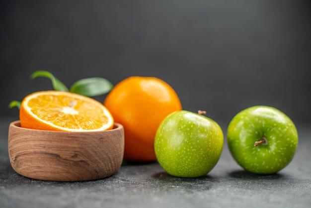 Vista lateral de la ensalada de frutas de beneficio con naranjas frescas y manzana verde en la mesa oscura