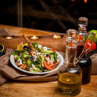 Vista lateral ensalada griega con aceite de oliva y salsa de soja y velas en plato blanco redondo