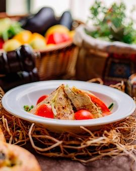 Vista lateral ensalada de pollo pollo a la parrilla con rodajas de tomate, pepino, queso y verduras en un plato