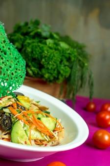 Vista lateral de ensalada de pollo con verduras frescas picadas y aceitunas negras en un tazón
