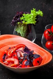 Vista lateral ensalada de tomate con cebolla y albahaca