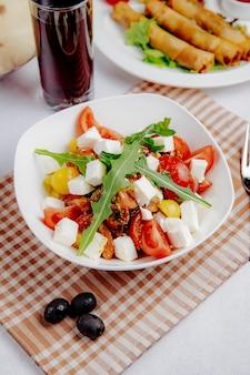Vista lateral de ensalada con tomate feta y rúcula