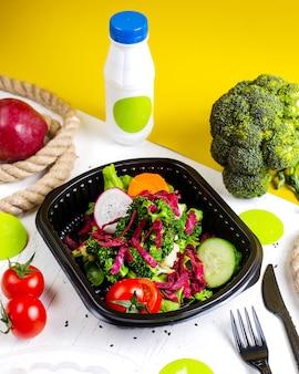 Vista lateral de la ensalada de vegetales frescos con rábano, col roja, zanahoria y brócoli en una caja de entrega sobre la mesa