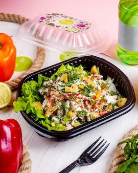 Vista lateral de ensalada de verduras con champiñones pimientos zanahoria eneldo y salsa de crema en la caja de entrega
