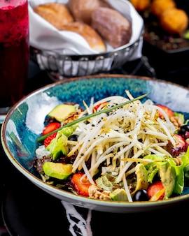 Vista lateral ensalada de verduras con frutas, fresas y uvas en un plato