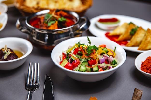 Vista lateral ensalada de verduras con pepino cebolla roja pimiento verde y pimienta negra en un plato